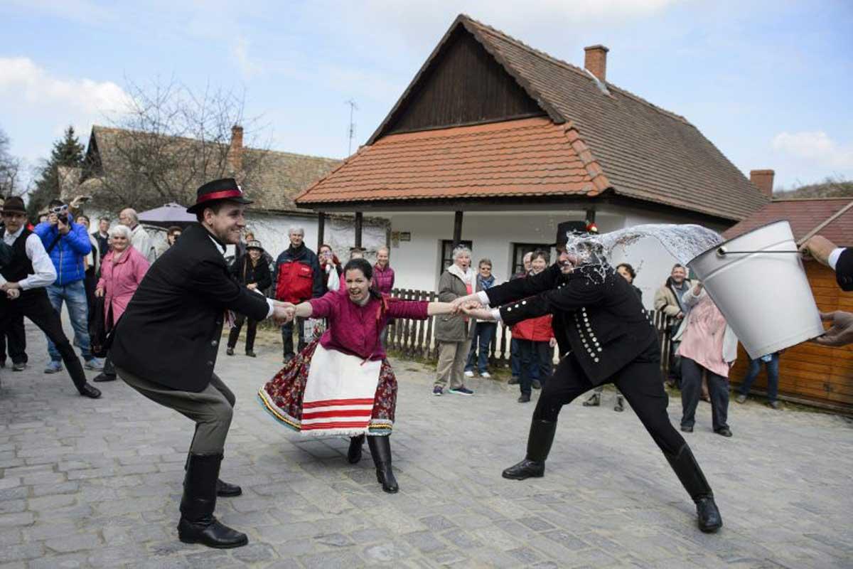 Népviseletbe öltözött fiatalok locsolkodnak Hollókő ófalujában – Fotó: MTI/Komka Péter